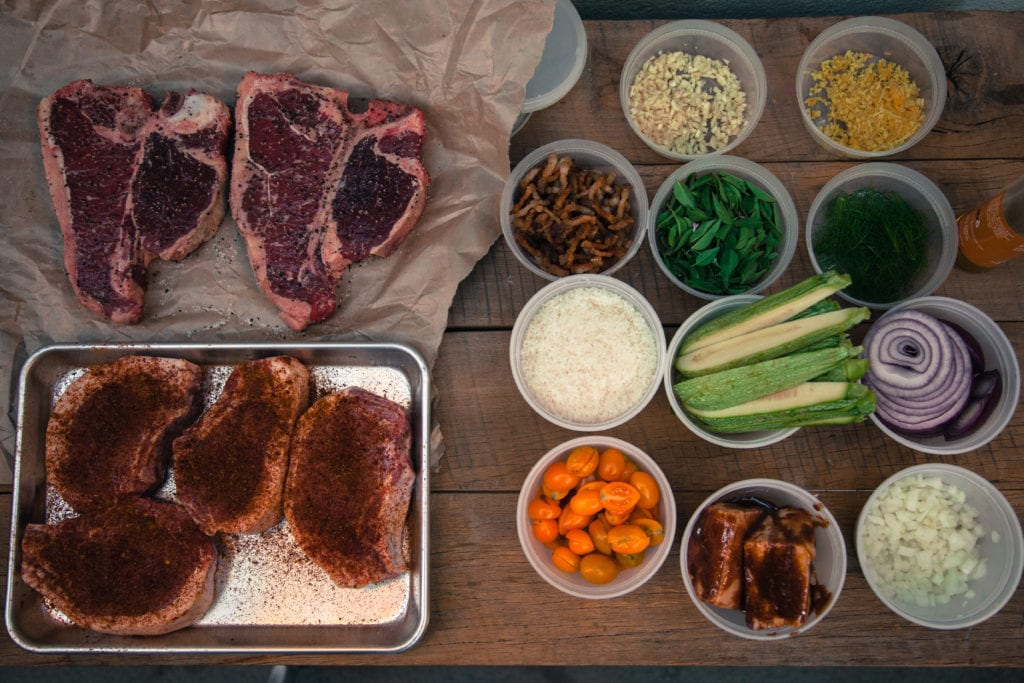 Meat, vegetables, and various herbs and spices on a wood table.